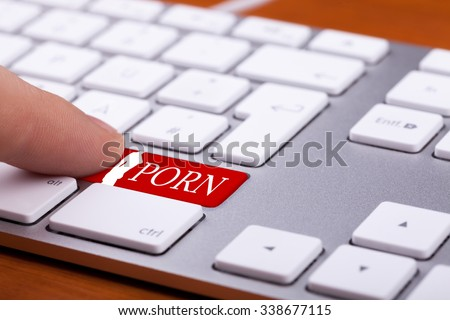 Finger pressing on red button with porn word and naked woman silhuette on it. Sex and xxx sites. Adult content only - stock photo