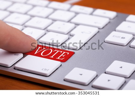Finger pressing on vote red button on keyboard. Online elections - stock photo