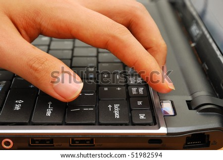 Finger pressing power button on laptop keyboard. For concepts such as electronics and technology, and office and business. - stock photo