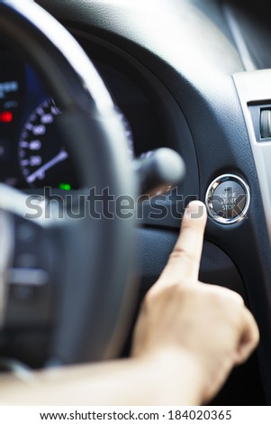 finger pressing the Engine start stop button - stock photo