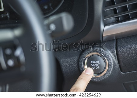 Finger pressing the Engine start stop button of a car
