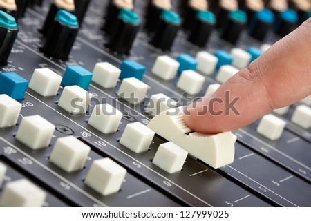 Finger pushing a mixing desk slider; shallow depth of field - stock photo