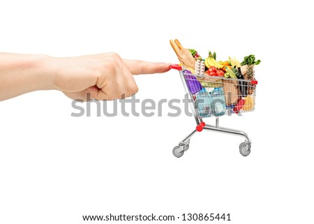 Finger pushing a shopping cart full of food products, isolated on white background - stock photo