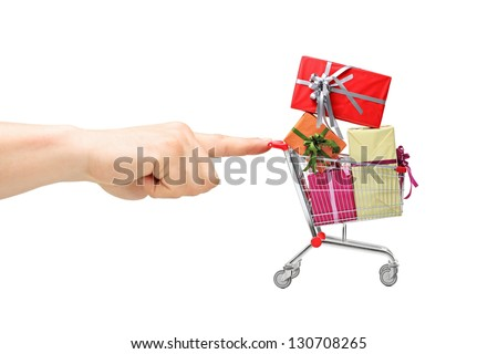 Finger pushing a shopping cart with presents, isolated on white background - stock photo