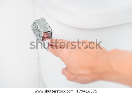 Finger pushing button and flushing toilet - stock photo