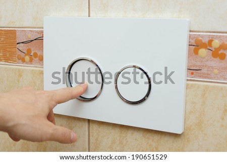 finger pushing button for  flushing toilet - stock photo