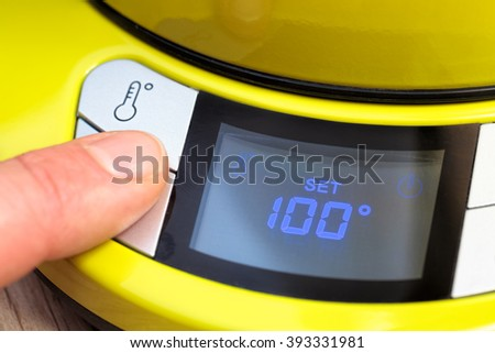 Finger pushing button on a digital thermostat control panel of electric tea kettle setting temperature to 100 degrees Celsius - stock photo