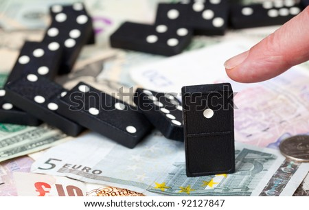Finger pushing last domino standing on pound, euro and dollar bank notes illustrating banking crisis or Brexit - stock photo
