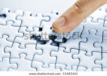 Finger pushing missing puzzle piece into place - stock photo