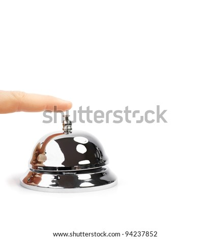Finger Pushing Service Bell. A finger pushing a shiny domed desktop service bell in a service, hospitality and help concept. - stock photo