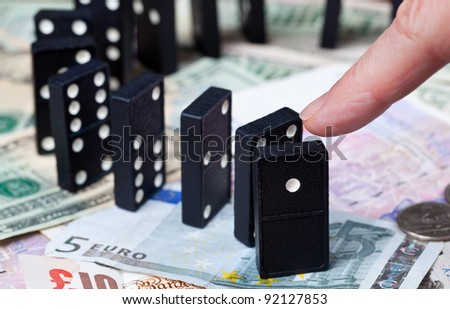 Finger pushing standing dominoes on pound, euro and dollar bank notes illustrating banking crisis - stock photo