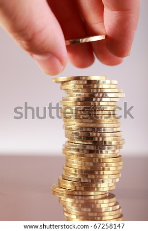 Finger put coin on coin-stack