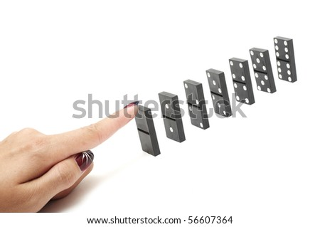 Finger ready to push over dominoes. Only the first domino in focus. - stock photo
