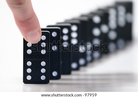 Finger ready to push over dominoes. Only the first domino in focus.