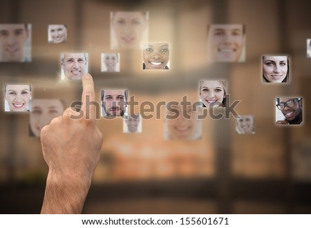 Finger selecting futuristic interface showing faces - stock photo