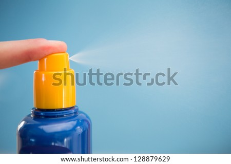 Finger spraying sun tan lotion with copy space on blue background - stock photo