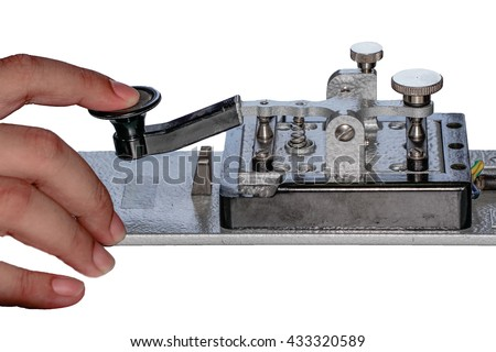 finger tapping on morse telegraph key - stock photo