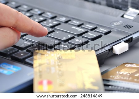 finger to button on the keyboard beside credit card, shopping online payment - stock photo