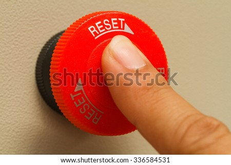 Finger touch on red emergency stop switch - stock photo