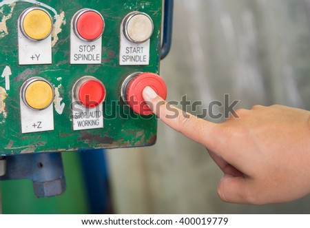 Finger touch on red emergency stop switch during machining in workshop. - stock photo
