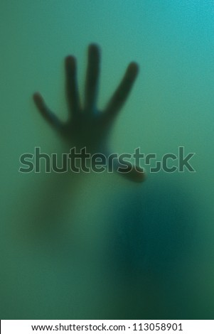 finger touch to frosted glass seem like ghost use for halloween - stock photo