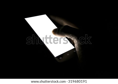 finger touch white screen Mobile telephone in the darkroom - stock photo