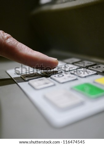 Finger using automatic teller keypad to enter pin number - stock photo