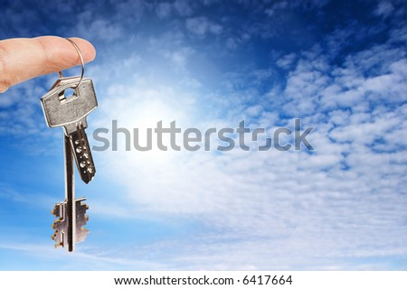 Finger with key on blue sky background - stock photo