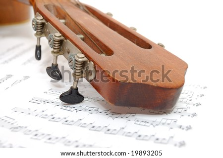 Fingerboard of old guitar under leaf with notes - stock photo