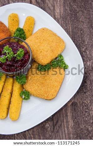 Fingerfood (fried Cheese) on a plate against wooden background