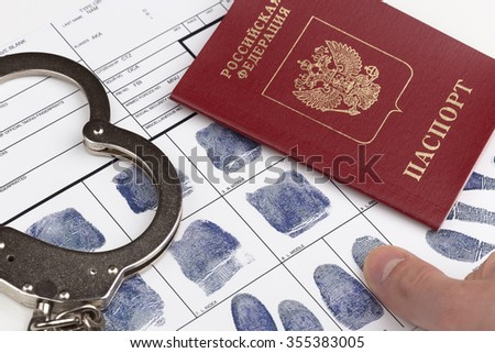 Fingerprint card with russian travel passport and handcuffs - stock photo