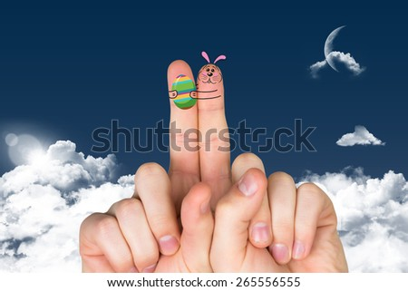 Fingers as easter bunny against night sky - stock photo