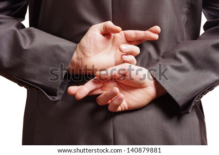 fingers crossed behind a suited backside - stock photo