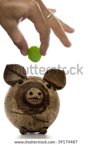Fingers depositing a green coin in a wooden piggy bank - stock photo