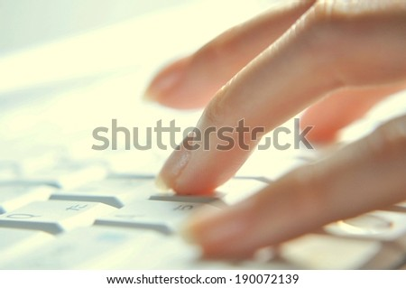 Fingers from one hand type words on a computer keyboard. - stock photo