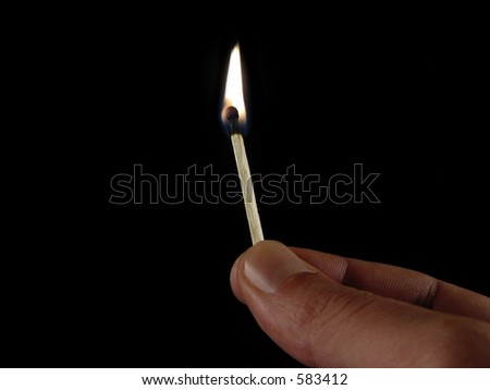 Fingers holding a match infront of black background