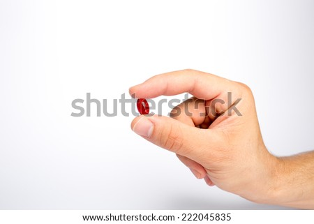 Fingers holding a red pill - stock photo