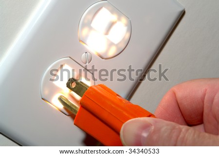 Fingers inserting a power cord plug into a glowing North American standard 110 volt electric wall outlet receptacle