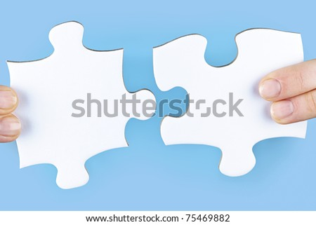 Fingers joining large white blank jigsaw puzzle pieces - stock photo