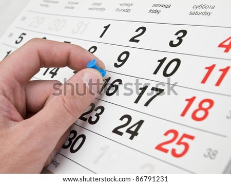 Fingers making marks on the calendar page - stock photo