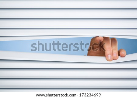Fingers of a female hand opening a peeking hole through closed shutters.