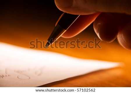 fingers of a hand holding an ink pen, about to sign a contract - stock photo