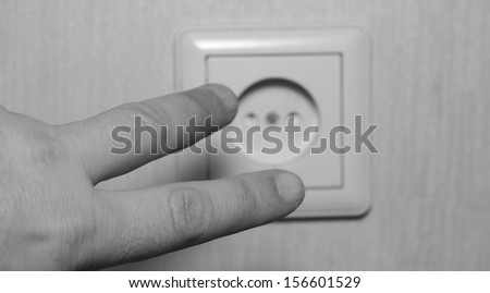 fingers on a hand about the electric socket