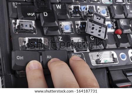 Fingers on alt ctrl delete keys on broken laptop keyboard - stock photo