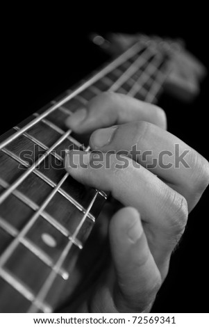 fingers on electrical bass guitar fretboard, black and white
