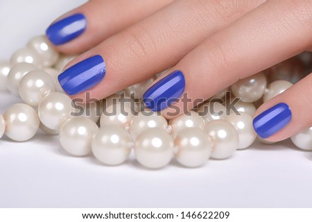 Fingers on pearls. Close-up of female hand covering a pearl necklace - stock photo