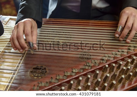 Fingers Playing Arabian Qanon Musical Instrument During a Symphony - stock photo
