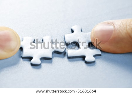 Fingers pushing two matching puzzle pieces together - stock photo