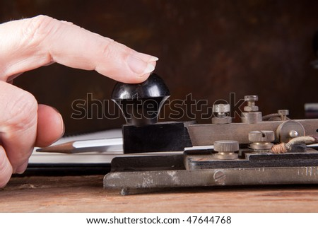 Fingers tapping morse code on an antique telegraph - stock photo