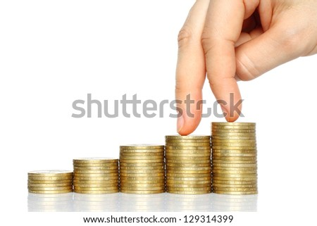 Fingers walking down on stacks of coins on white background. Decline concept - stock photo
